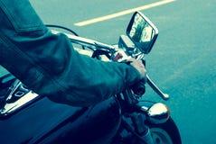 在一辆摩托车的气体的手在路的 库存照片