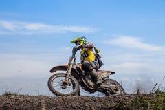 在一辆摩托车的男性车手在山顶部 免版税图库摄影