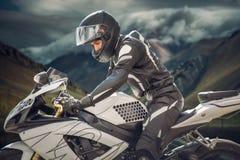 在一辆摩托车的车手有首要山的作为背景 云彩的山 库存照片