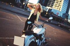 在一辆摩托车附近的美好的少妇白肤金发的身分在b 免版税库存图片