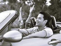 在一辆敞篷车汽车的年轻亚洲夫妇骑马 免版税库存照片