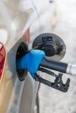 在一辆新的汽车的汽油箱的气泵喷管 免版税库存图片