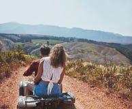 在一辆方形字体自行车的年轻夫妇骑马在乡下 免版税图库摄影