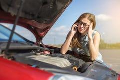 在一辆残破的汽车附近的女孩在乡下公路 免版税库存照片