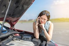 在一辆残破的汽车附近的女孩在乡下公路 库存图片