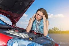 在一辆残破的汽车附近的女孩在乡下公路 图库摄影