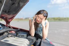 在一辆残破的汽车附近的女孩在乡下公路 库存照片