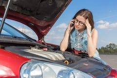在一辆残破的汽车附近的女孩在乡下公路 免版税图库摄影
