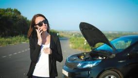 在一辆残破的汽车附近的妇女在路要求协助 年轻担心的女孩使用一个电话解释 股票录像