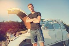 在一辆残破的汽车附近的年轻人 免版税库存图片