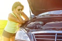 在一辆残破的汽车附近的沮丧的妇女司机 在国家的机器 库存照片