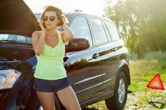 在一辆残破的汽车附近的沮丧的妇女司机 在国家ro的一辆汽车 库存图片