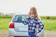 在一辆残破的汽车附近的少妇要求帮助 库存图片