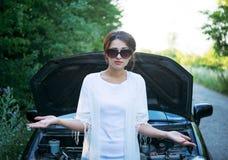 在一辆残破的汽车附近被混淆的女孩立场 免版税库存图片