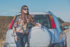 在一辆汽车旁边的一条离开的路上有一个美丽的女孩的 库存图片