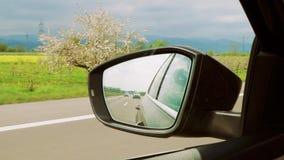 在一辆汽车的后视镜和汽车和高速公路看见的山在德国