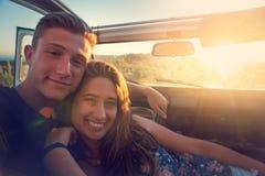 在一辆汽车的夫妇在日落 库存照片