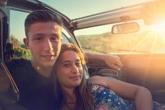 在一辆汽车的夫妇在日落 库存图片