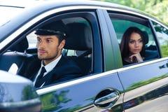 在一辆汽车的妇女骑马有汽车夫的 库存图片