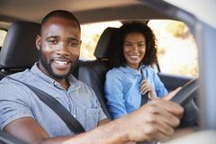 在一辆汽车的年轻黑夫妇在微笑对照相机的旅行 免版税库存照片