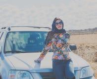 在一辆汽车附近的可爱的孤独的女孩在一条偏僻的路 免版税图库摄影
