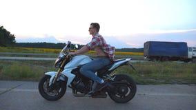 在一辆现代体育摩托车的年轻人骑马 驾驶他的摩托车的衬衣和玻璃的英俊的摩托车骑士  股票录像