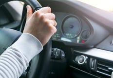 在一辆现代汽车的方向盘的美好的妇女` s手 拿着方向盘的手 驾驶现代汽车的妇女 户内汽车内部皮革速度炫耀通信工具 库存照片