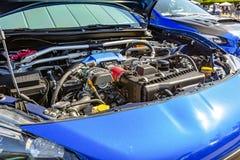 在一辆现代蓝色汽车的敞篷的下引擎 图库摄影