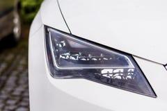 在一辆现代白色昂贵的白色汽车的前灯 免版税库存照片