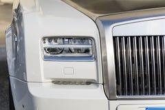 在一辆现代白色昂贵的白色汽车的前灯 免版税库存图片