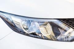 在一辆现代白色昂贵的白色汽车的前灯 库存图片