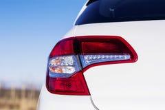 在一辆现代白色汽车的红色前灯 图库摄影