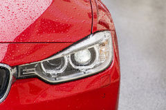 在一辆现代红色昂贵的湿汽车的前灯 免版税库存图片