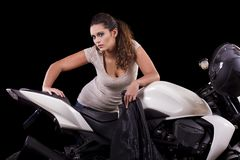 在一辆白色摩托车旁边的美丽的女孩 免版税库存照片