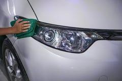 在一辆白色汽车的手清洗的汽车车灯 免版税库存照片