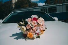 在一辆白色汽车的敞篷的婚礼花束 免版税库存图片