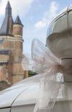 在一辆白色汽车的桃红色丝带在婚礼地点 免版税库存照片