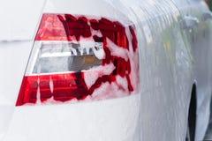在一辆白色汽车的红色尾灯在水槽的没有接触的泡沫 免版税库存图片
