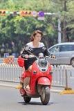 在一辆红色减速火箭的样式e自行车的俏丽的gril,昆明,中国 免版税图库摄影