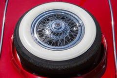 在一辆红色减速火箭的汽车的备用轮胎 免版税库存图片