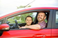 在一辆红色汽车的夫妇 库存照片