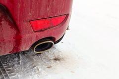 在一辆红色汽车的排气管的细节在雪停放了 库存照片