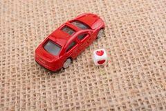 在一辆红色玩具汽车的心脏立方体 免版税图库摄影