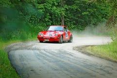 在一辆红色葡萄酒保时捷911 S赛车的未认出的司机 库存照片