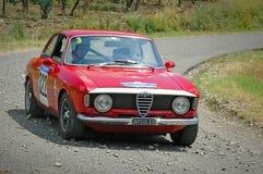 在一辆红色葡萄酒阿尔法・罗密欧朱莉娅105赛车的未认出的司机 免版税库存图片
