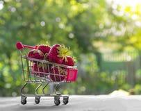 在一辆绿色背景圆的bokeh台车上用莓果红色草莓安置题字 库存照片