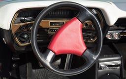 在一辆老优等的汽车的红色方向盘 图库摄影
