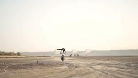 在一辆老摩托车的美好的少妇骑马和做把戏 在日落或日出的沙漠 女性骑自行车的人 稳定 影视素材