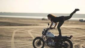 在一辆老摩托车的美好的少妇骑马和做把戏 在日落或日出的沙漠 女性骑自行车的人 稳定 股票录像