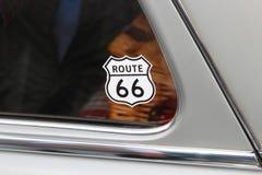 在一辆老汽车的窗口的路线66贴纸 库存图片